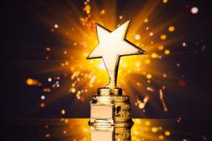 gold star trophy against shiny sparks background emitted from sparkler